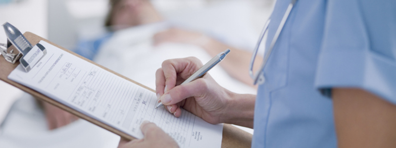 Health & Social Care Blog Header Image. Featuring Female Nurse Writing Entries Into A Medical Chart. Search Consultancy