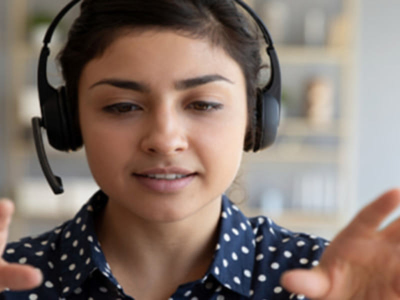 Woman wearing a headset managing her team remotely.