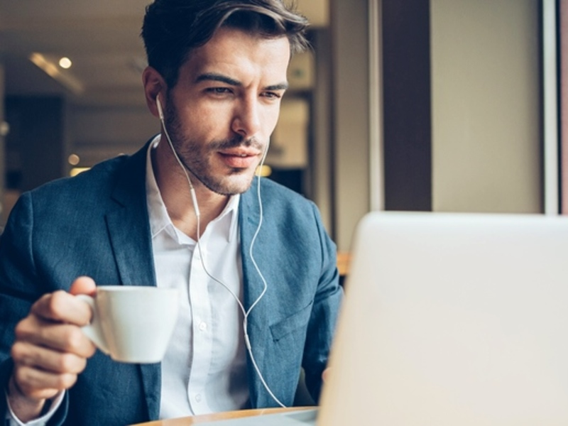 5 Best Payroll Blogs to follow blog header image. Featuring a male Payroll Manager with brown hair and dressed in a grey suit as he sits in a coffee shop browsing for the best payroll blogs. Search Consultancy.